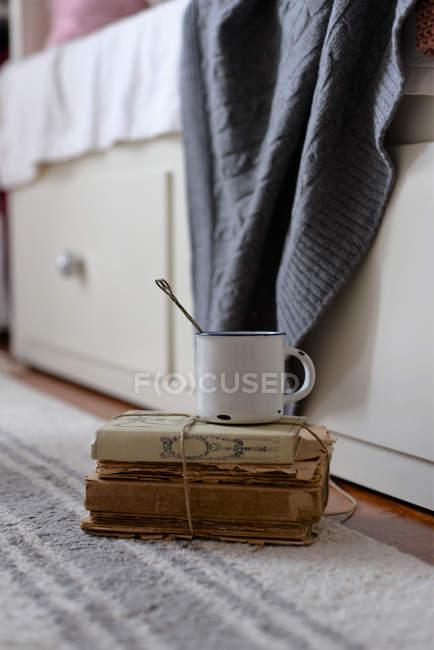 Старинная металлическая кружка с ложкой на куче антикварных книг — стоковое фото