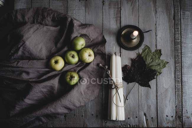 Still life of apples, candles and leaves on wooden table — Stock Photo