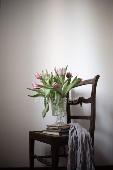 Still life of tulips in vase with pile of books on chair — Stock Photo