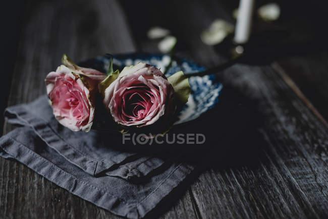 Розовые розы в винтажной керамической чаше на деревенском столе — стоковое фото