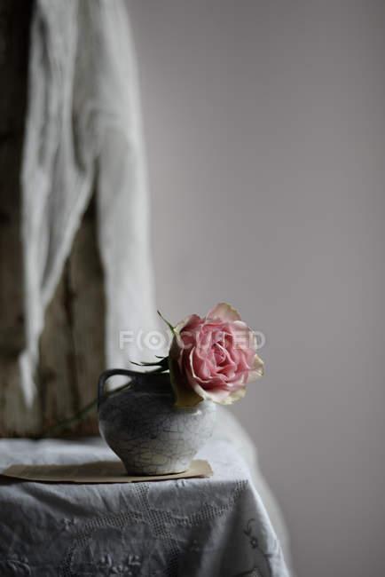 Розовый цветок розы в винтажной керамической вазе на столе — стоковое фото