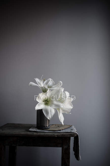 White lily flowers in vase on table — Stock Photo