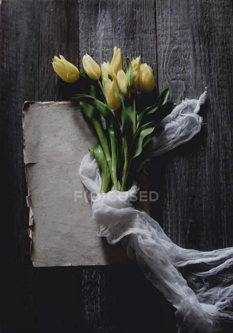 Куча желтых тюльпанов, завернутых в тюль на деревенском столе — стоковое фото