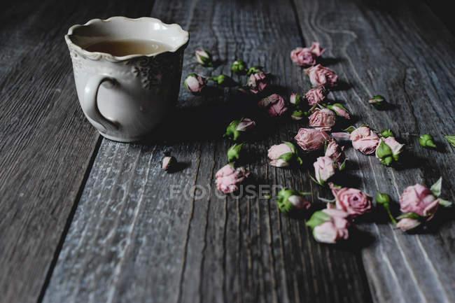 Розовые цветы разбросаны по столу с чашкой чая — стоковое фото