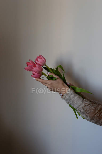 Female hands holding bunch of pink tulips — Stock Photo