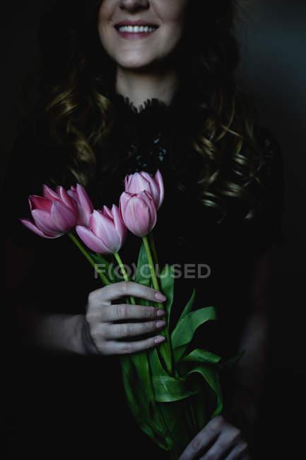Куповані подання молодої жінки, що тримає купу рожеві тюльпани. — стокове фото