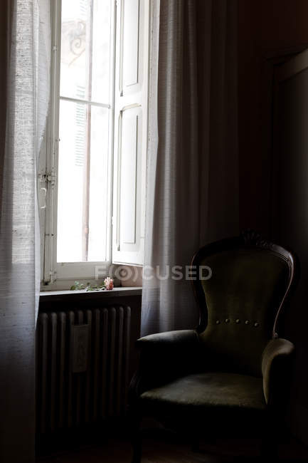 Room interior with armchair and flower on window sill — Stock Photo
