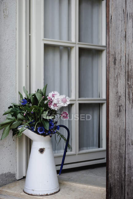 Floral arrangement with colorful cornflowers in metal jug on porch — Stock Photo