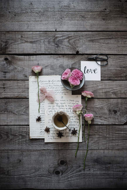 Still life of cup of green tea on table with handwritten notes and pink roses — Stock Photo