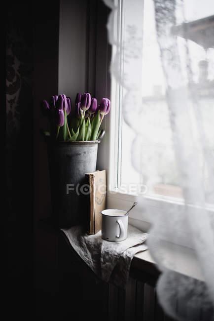 Bucket of freshly cut tulips on window sill with vintage book and enamel mug — Stock Photo
