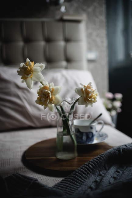 Fleurs Narcisse dans un vase en verre sur plateau en bois avec tasse vintage dans la chambre — Photo de stock