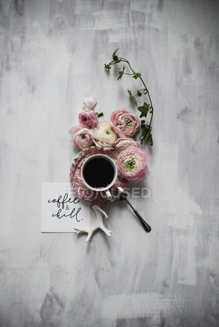 Cup of coffee on table with persian buttercup flowers — Stock Photo