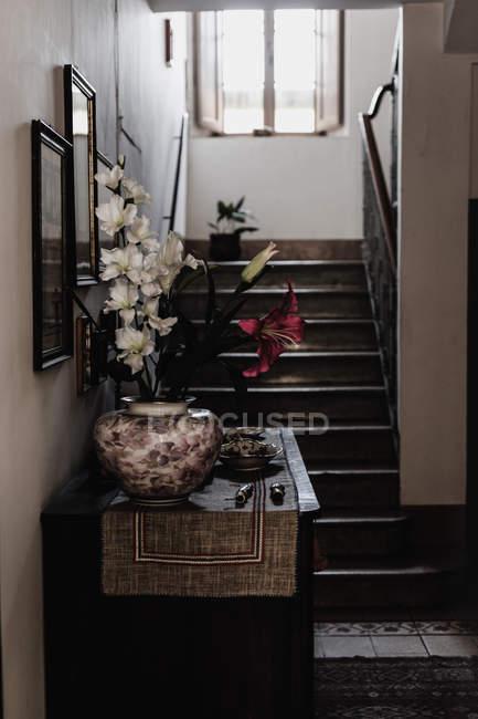 Intérieur de la maison avec décoration de fleurs de Lys sur le bureau par un escalier — Photo de stock
