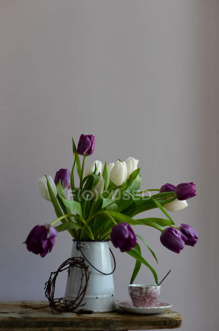 Purple and white tulips in jug on table with cup of coffee — Stock Photo