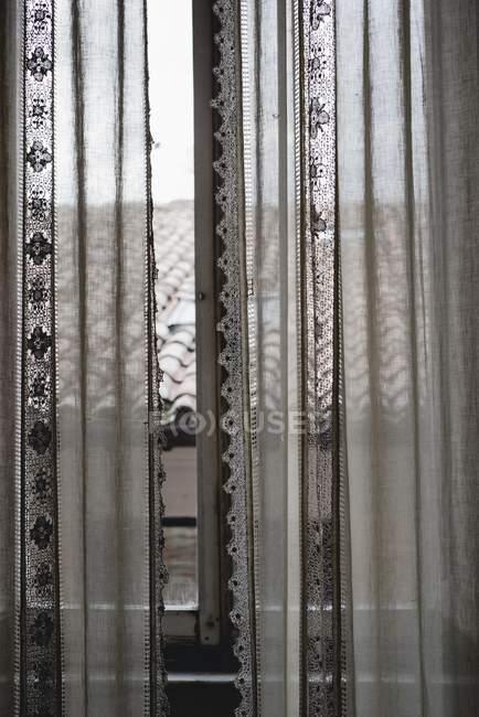 Cortinas que cubren la ventana rústica con vista del techo de la casa de país - foto de stock