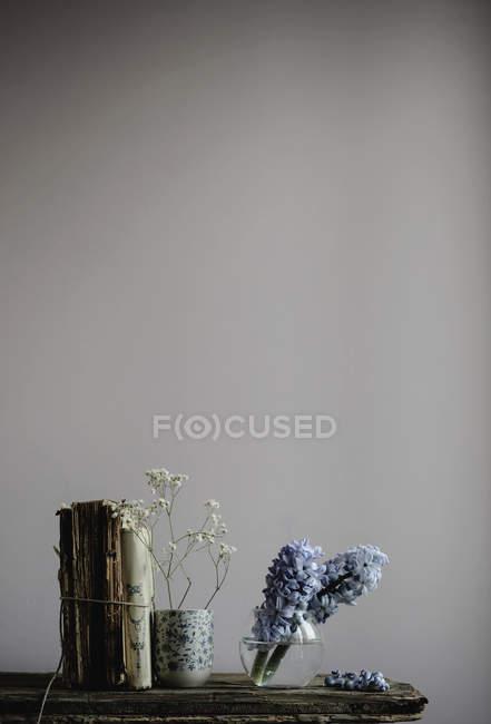 Натюрморт из голубой гиацинты и гипсофилы цветы, винтажные чашки и древние книги на полке — стоковое фото