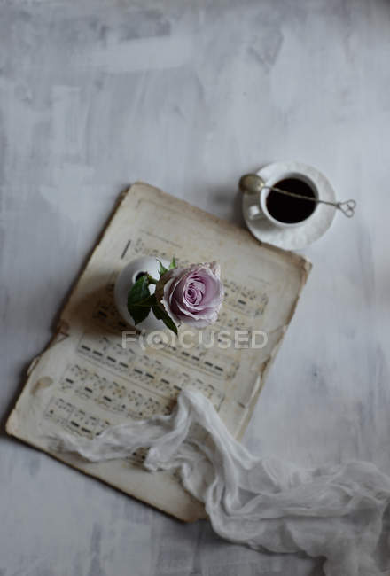 Pink rose on table with cup of coffee and sheet music — Stock Photo