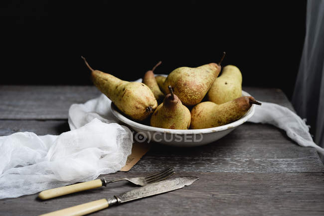 Still life with pears with vintage cutlery on rustic table — Stock Photo
