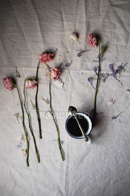Чашка кофе со старинной ложкой и розовыми цветами и лепестками на столе, вид сверху — стоковое фото