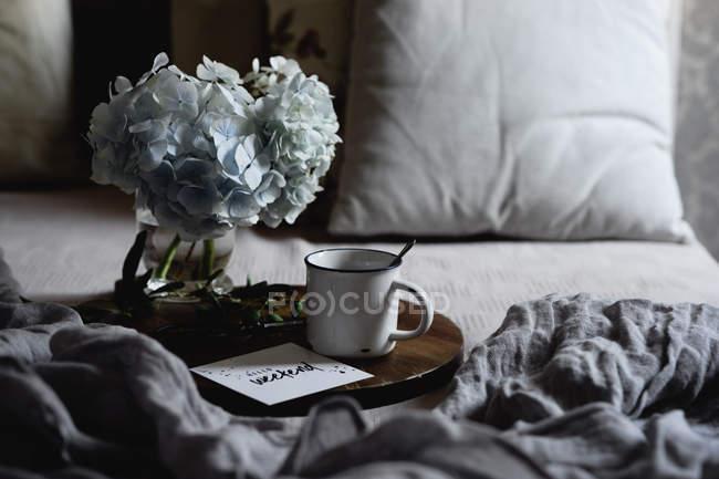 Tazza smaltata con caffè, ortensia bianca fiori su vassoio di legno in camera da letto — Foto stock
