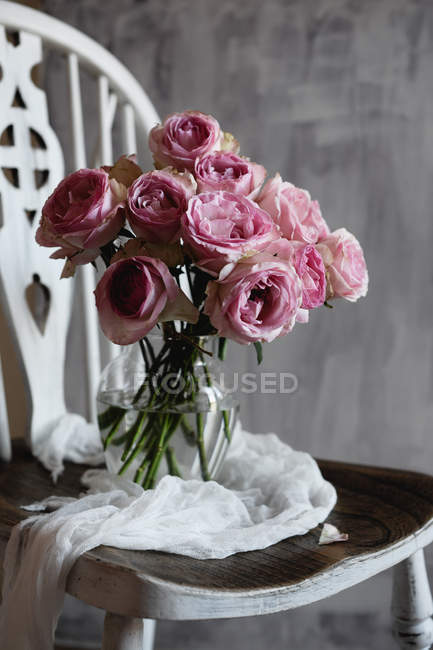 Bunch of pink rose flowers in glass jug on vintage chair — Stock Photo