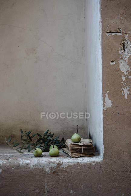 Grüne Birnen auf Haufen von alten Papieren in schäbigen Wandnische — Stockfoto
