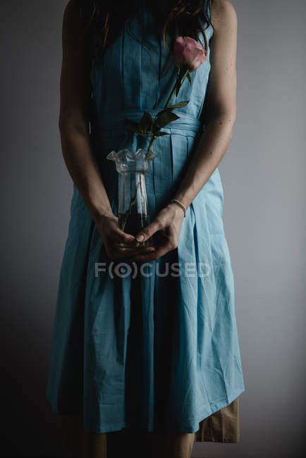 Abgeschnittene Ansicht des Teenie-Mädchens mit einer Vase mit einer einzigen rosa Rose — Stockfoto