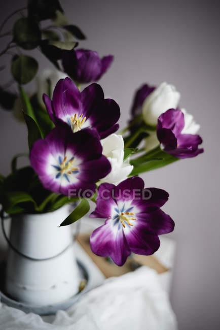 Nahaufnahme eines blühenden Straußes lila Tulpen im Krug auf dem Tisch — Stockfoto