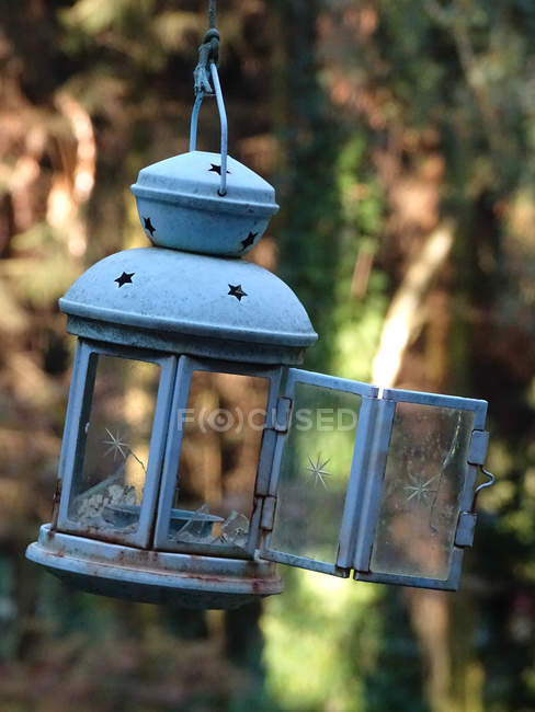 Vintage blue candle lantern with open door hanging outdoors — Stock Photo