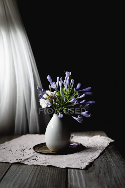 Floral decoration with agapanthus flowers in ceramic vase on table — Stock Photo