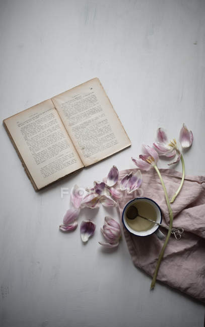 Enamel mug of green tea with tulip petals and open book — Stock Photo
