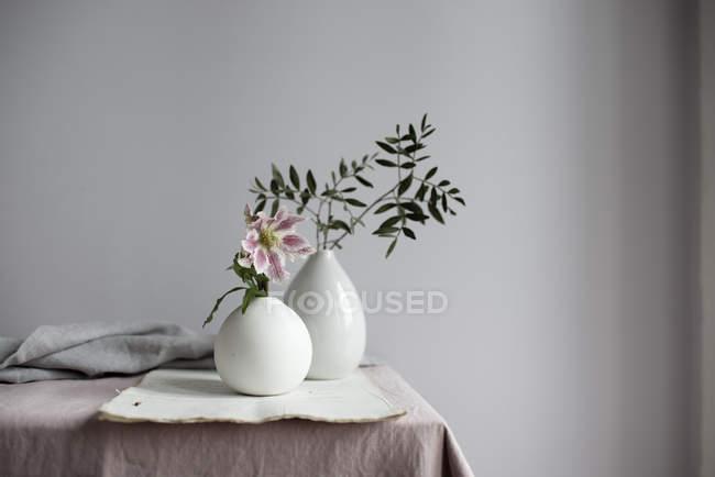 Flor de lírio cor de rosa e galhos de folhagem planta em vasos na mesa — Fotografia de Stock