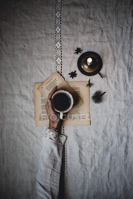 Braço feminino segurando xícara de chá preto na mesa com folhas de livro e vela — Fotografia de Stock