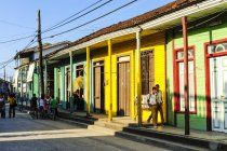 Cuba, Guantanamo, Baracoa, view of colored houses and people walking on sidewalk — Stock Photo