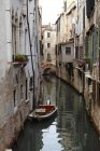 Italy, Venice, old houses and boat over canal water — Stock Photo