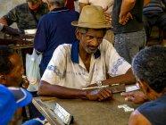 Зрелый человек в соломенной шляпе, сидя за столом, Куба, Гавана — стоковое фото