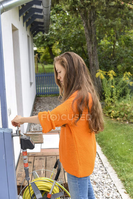 Young woman adjusting water tap against house at garden — Stock Photo