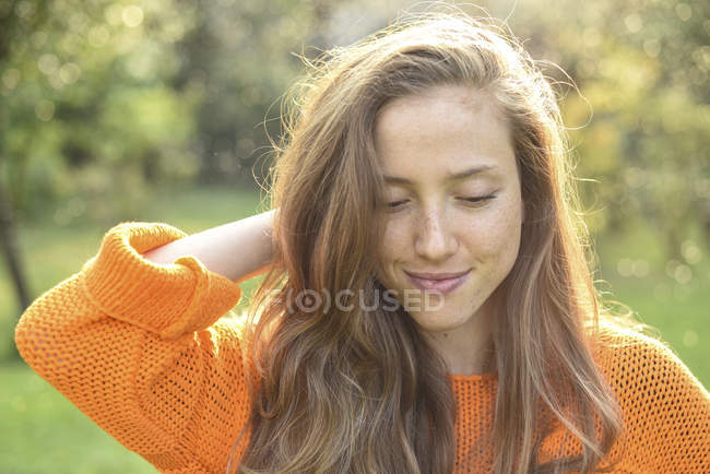 Portrait of young smiling woman looking down with hand behind head — Stock Photo
