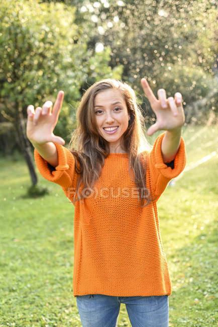 Jeune souriant à orange manteau cadres gesticulant de doigts au jardin — Photo de stock