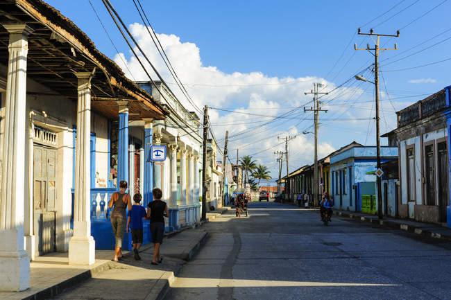 Куба, Гуантанамо, Баракоа, просмотр цветных домов и людей, идущих на тротуаре — стоковое фото