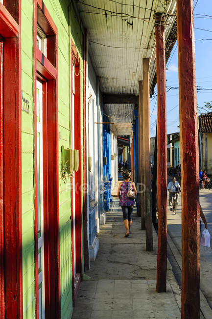 Cuba, Guantanamo, Baracoa, view of colored houses and person on sidewalk — стоковое фото