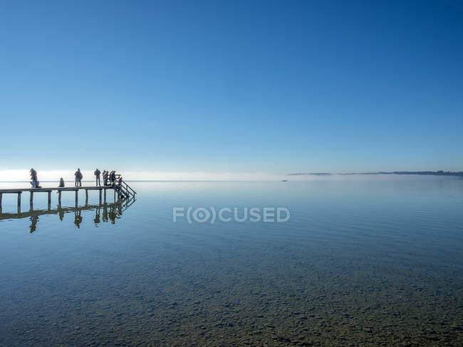 Menschen im Herbst auf einem Steg am Starnberger See bei Ambach ...