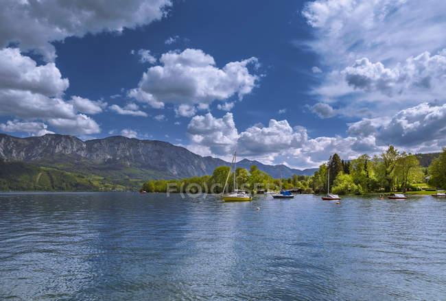 Lac avec des bateaux sur la surface de l'eau, Mondsee dans le Salzkammergut, Autriche — Photo de stock