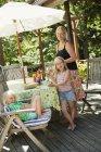 Madre e figlie che mangiano hot dog in giardino — Foto stock