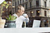 Man wearing white shirt drinking tea and looking at laptop — Stock Photo
