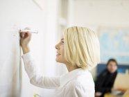 Frau schreiben auf Whiteboards, Mann im Hintergrund — Stockfoto