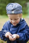 Boy with handful of bilberries, selective focus — Stock Photo