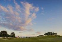 Croix lointaine sur champ vert sous ciel nuageux bleu — Photo de stock