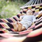 Niña, acostado en la hamaca, foco en los pies descalzos - foto de stock