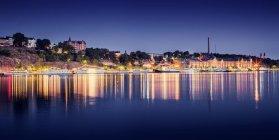 Bâtiments côtiers éclairés la nuit réfléchissant dans l'eau — Photo de stock